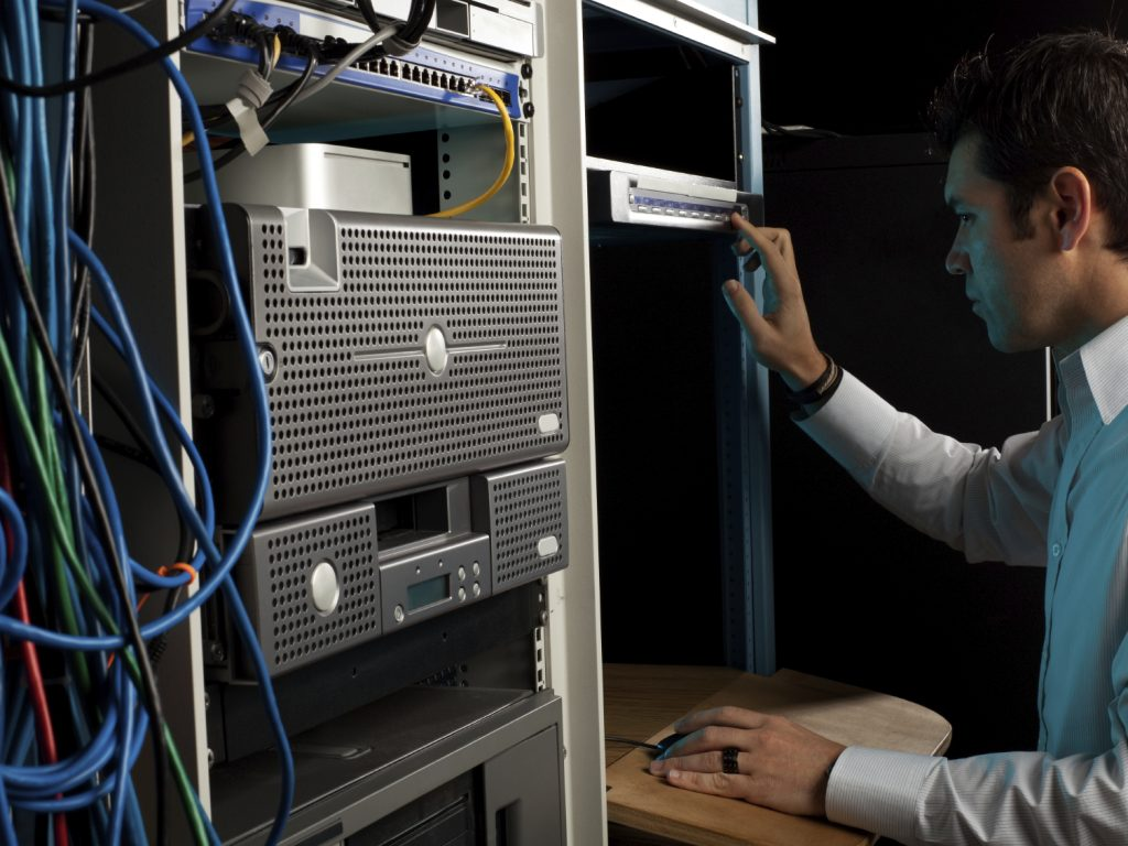 An IT technician programming on a computer